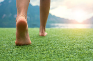 person's feet walking on the grass