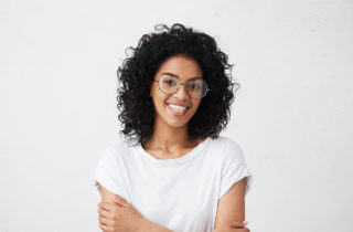 Young African-American woman in glasses smiling.