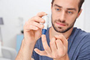 man tests blood sugar levels