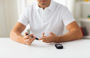 man tests diabetes blood sugar
