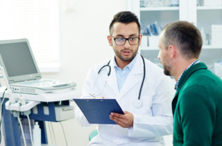 middle-aged man talks to doctor about prostate exams