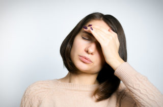 Woman with hand on forehead suffering from a headache