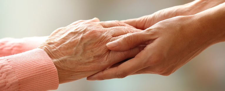 elderly woman's hands being held by a hospice volunteer.