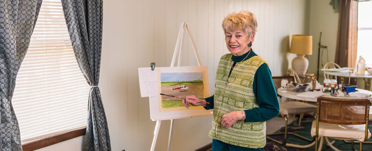 Dolores Ott, a stroke patient, poses next to her painting of an OSF LIfeFlight helicopter