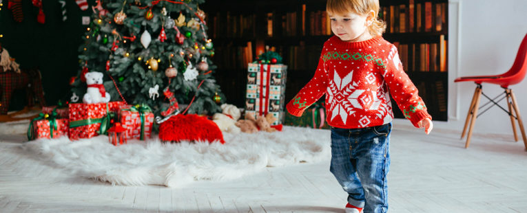 Toddler in sweater by a Christmas tree.