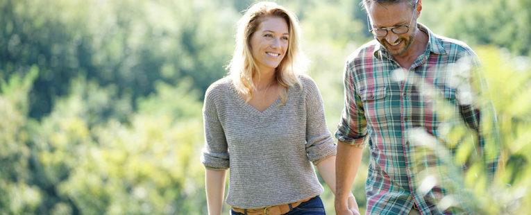 Man and Woman Walking in Field