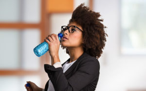 African-American businesswoman drinking bottled water