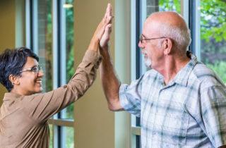 Joe Osborne give a high five to Sara Glassgow, MD, after surgery