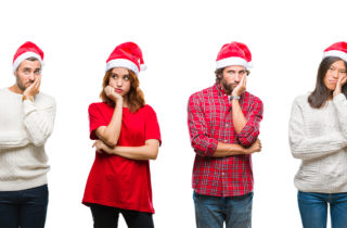 Several people suffering from holiday grief wearing Santa Claus hats.