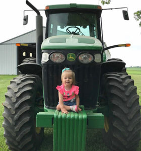 Adalie Guth sitting on a tractor