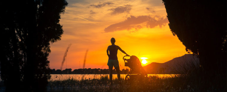 woman and child in stroller on a beach at sunset