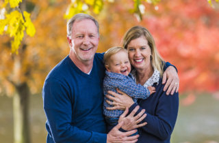 Rick and Angela Farnan along with their son, Blaze standing outside in autumn.