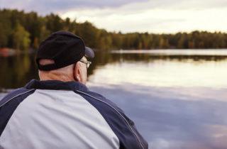 senior man contemplating while staring at a lake outside