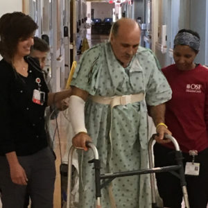 Dennis VanMeter walking in the hospital with nursing staff.