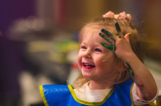 Cheerful Adalie Guth playing with finger paint at home.