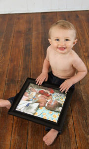 Baby Elliott at home with a photo of himself as a newborn