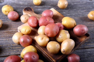 Red and Yukon Gold potatoes on a rustic cutting board.