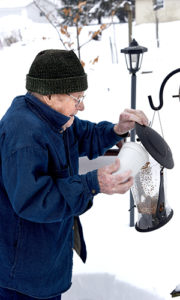 James Nelson refilling a bird feeder in winter
