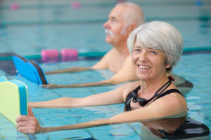 senior woman and man exercising in a pool