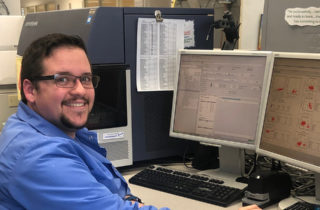 Joshua Barrett, Clinical Laboratory Scientist. He is working in our Flow Cytometry department, analyzing sample results and graphs.