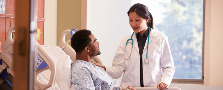 Physician consulting with patient in hospital shortly before surgery