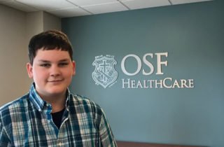 Kaleb stands by OSF HealthCare Children's Hospital sign