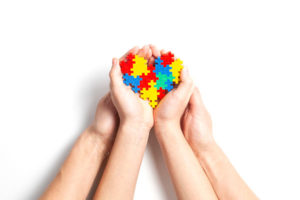 child and adult hands with puzzle pieces