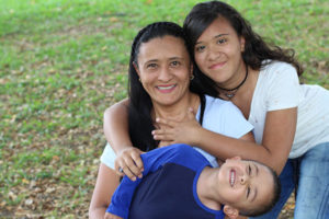 Hispanic mother with young boy with autism and teenage daughter.