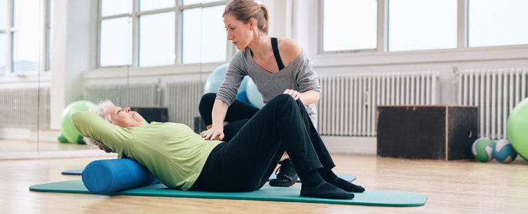 senior woman doing pelvic floor exercises in gym with trainer