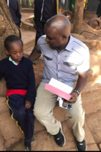 Michelle and Wismark reading a letter in Kenya
