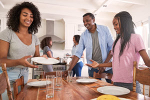 African-American family clearing dishes from the breakfast table after mindful eating.
