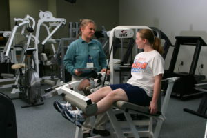 sports medicine specialist working in gym with student athlete