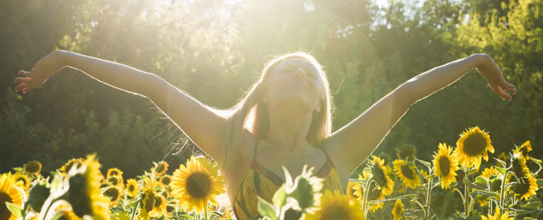 Woman stretching and relaxing in field of sunflowers