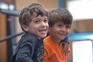 Two young brothers smiling at Autism Collective