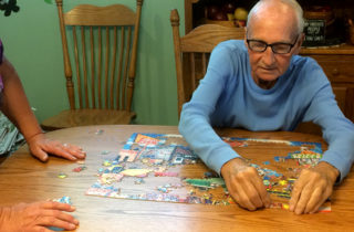 Harry and Terry Alexander putting a jigsaw puzzle together in their dining room