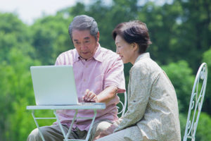 senior couple outdoors researching Medicare plans on laptop
