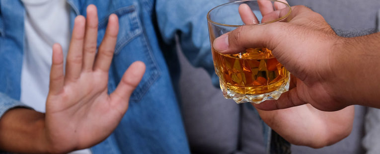 person saying no to friend offering glass of whiskey