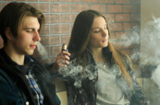 Teenage boy and girl vaping