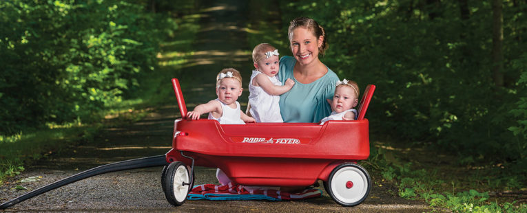 Colwell triplets and their mother in a wagon outdoors.
