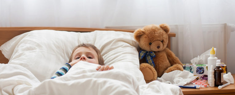 Male toddler with fever in bed