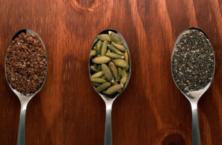 Flax seeds, pumpkin seeds, and chia seeds on spoons