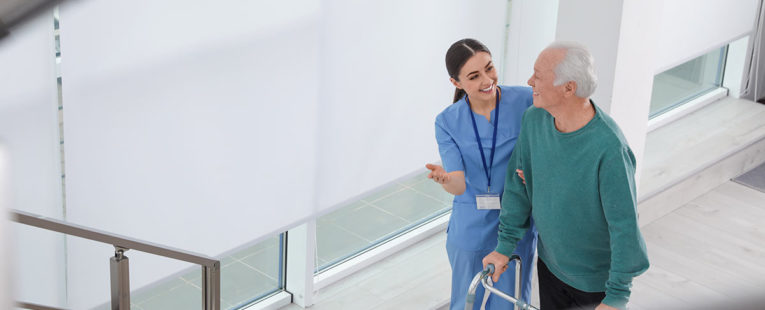 Physical Therapist walking with senior male patient in hallway