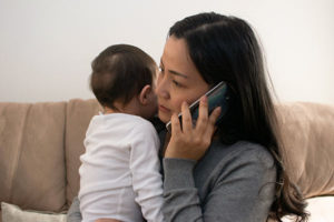 young mother holding with infant with fever calling