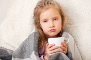 young girl with a fever wearing a blanket and drinking hot tea
