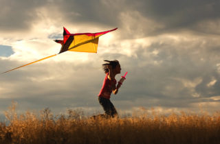 Young girl running in wheat field with kite under cloudy skies
