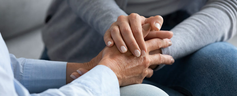 Grief support group participants holding hands