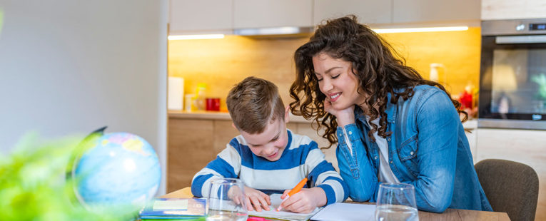 Young mother with son at kitchen table doing homework