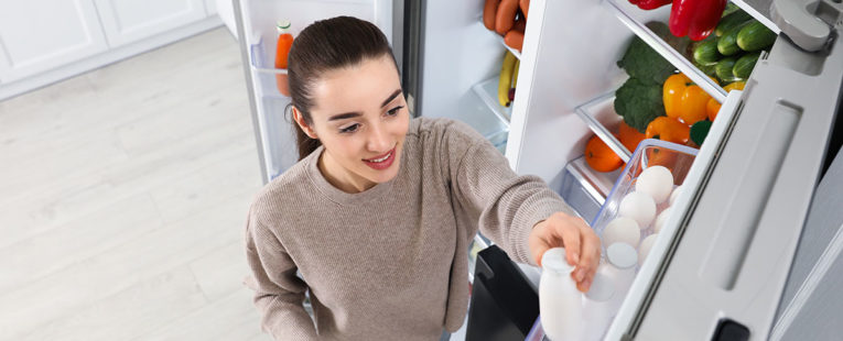 Young woman getting beverage out of refrigerator.