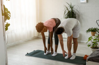 Couple exercising in their apartment.