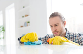 Young man cleaning kitchen countertop with gloves and cleaning solution.